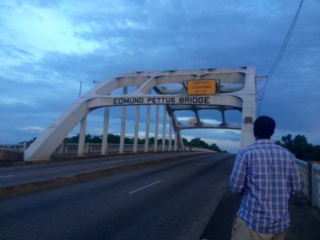 A black man n a patterned blue shirt faces the Edmund Pettus Bridge in Selma, AL, at sunset.